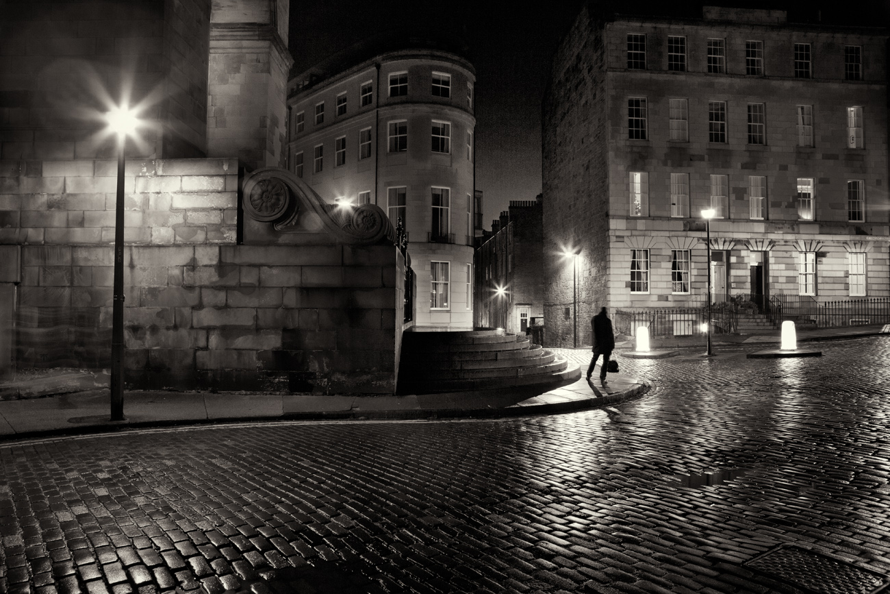 night photo of a man in a hat on a street corner in Edinburgh's Stockbridge