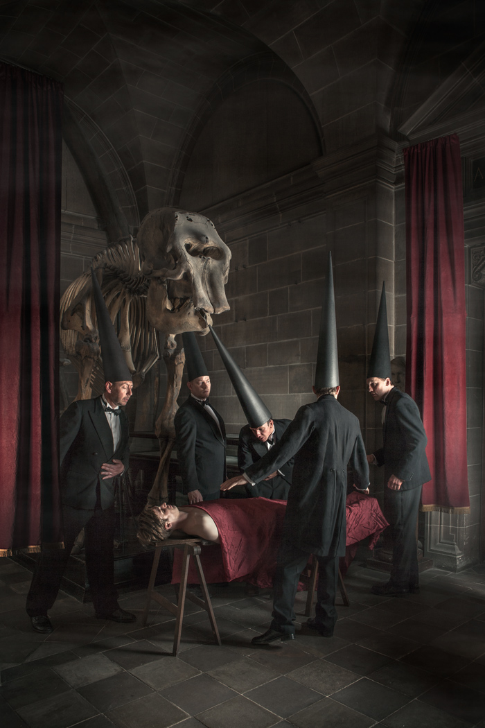 Conemen at an operating table by an elephant skeleton