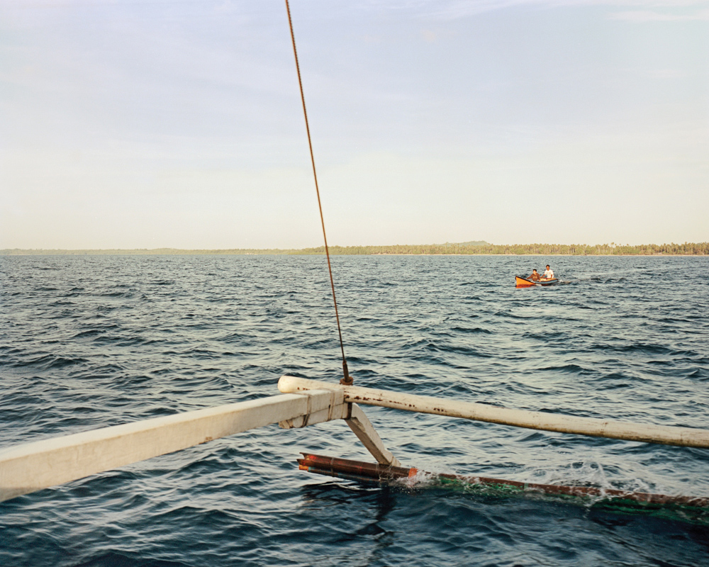 A passenger is brought to an outrigger boat headed to Balabac.