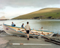 Rowers from the Miðvágs Róðrarfelag clean their boat after practice.