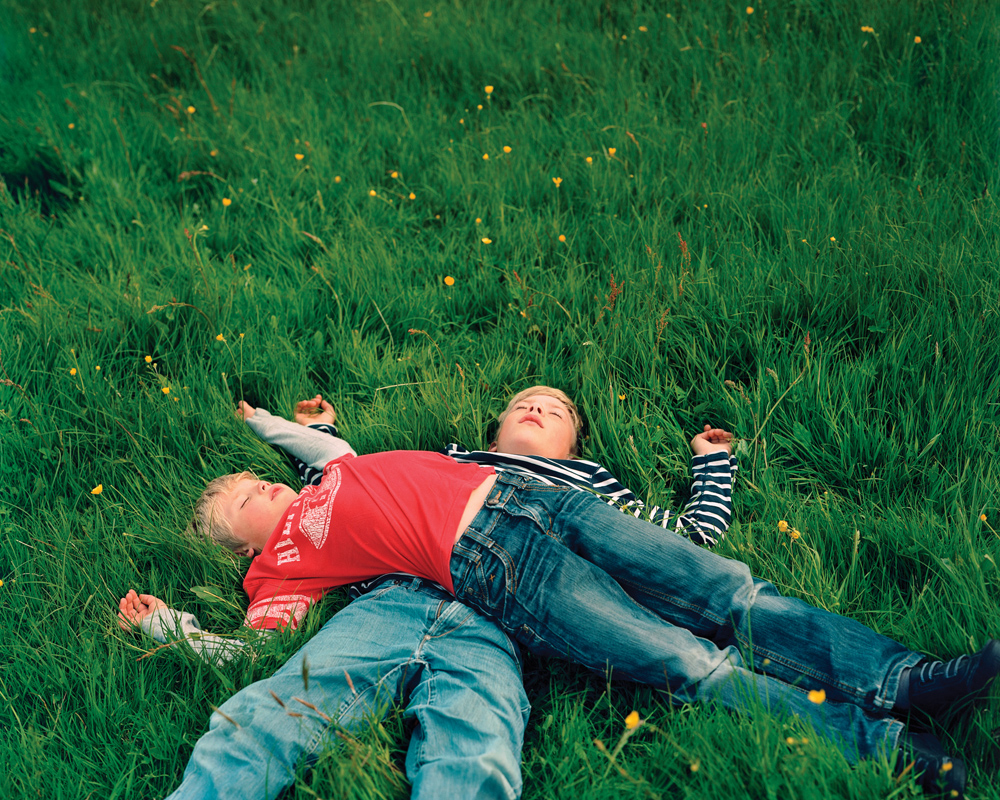 Noah and David rest in the grass after playing.