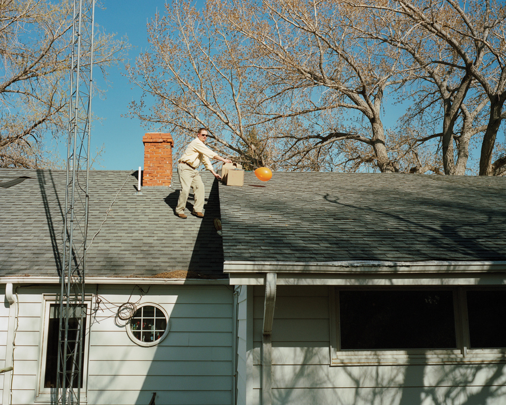 Glen Kirkbride throws Easter egg boxes off the roof of his house to judge which best protects the raw egg inside.