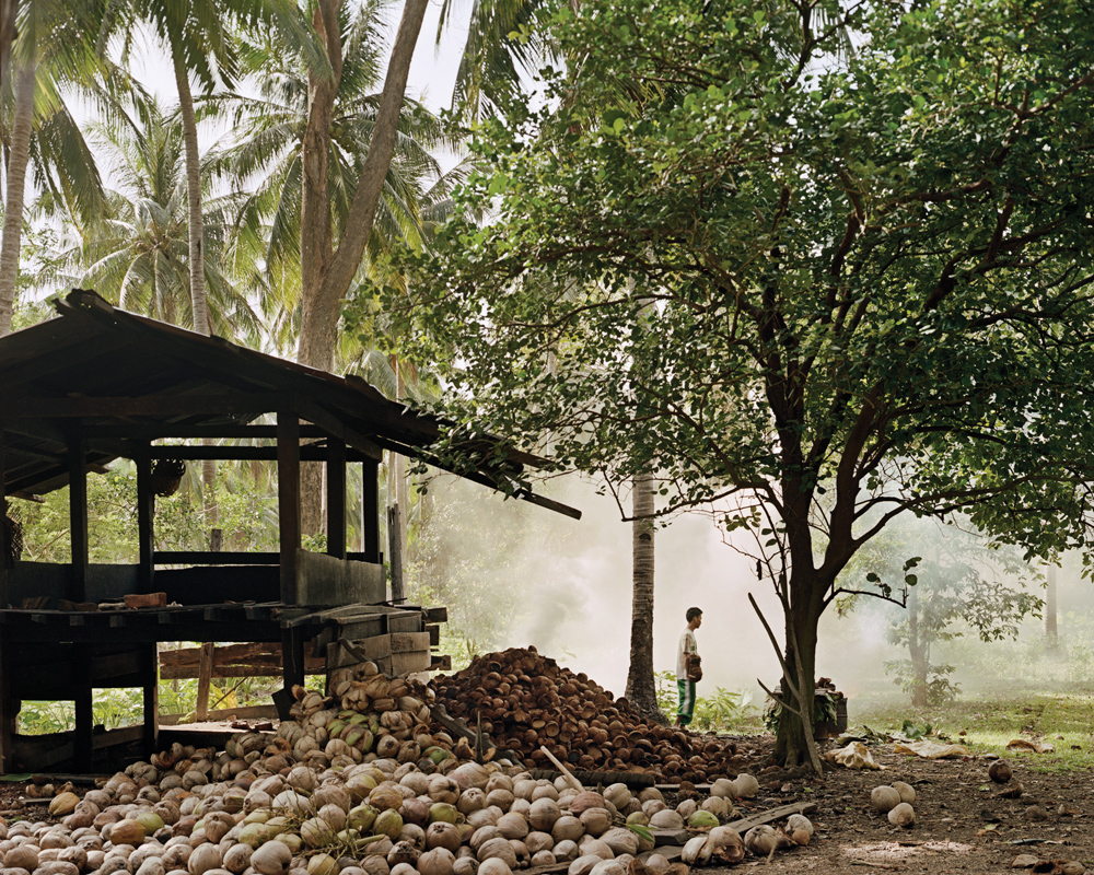 Rolando's son helps him burn coconut shells to make charcoal.