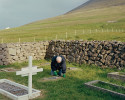 An old man cleans gravestones in the Lutheran cemetery.