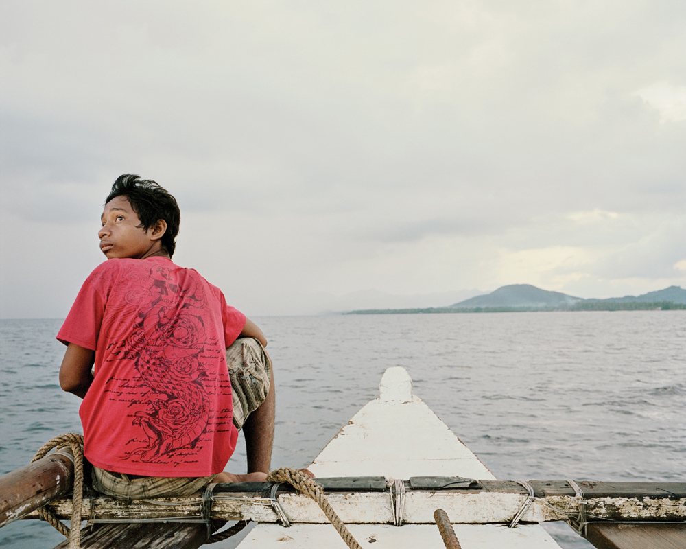 A young man sits on the bow of an outrigger boat approaching Balabac.