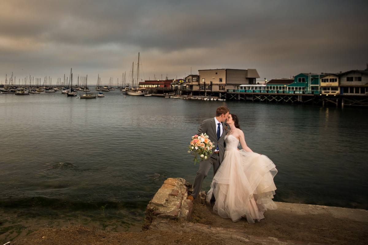 bride and groom in old downtown monterey taking wedding photos at sunset