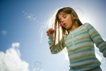 Young girl with a striped shirt blowing bubbles with a blue sky behind her shot for Stericycle ad campaigns.