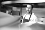 Black and white image of a chef working in a kitchen.
