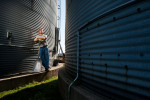 Working Farmer shot for Unity Seeds standing between two grain storage bins.