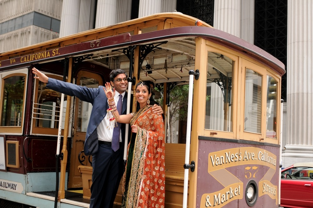 Hindu / Indian Wedding Photography Hindu couple riding on San Francisco cable car.  Photography by Bay Area Indian Wedding Photographer