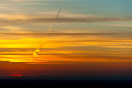 jet trail through clouds at sunset