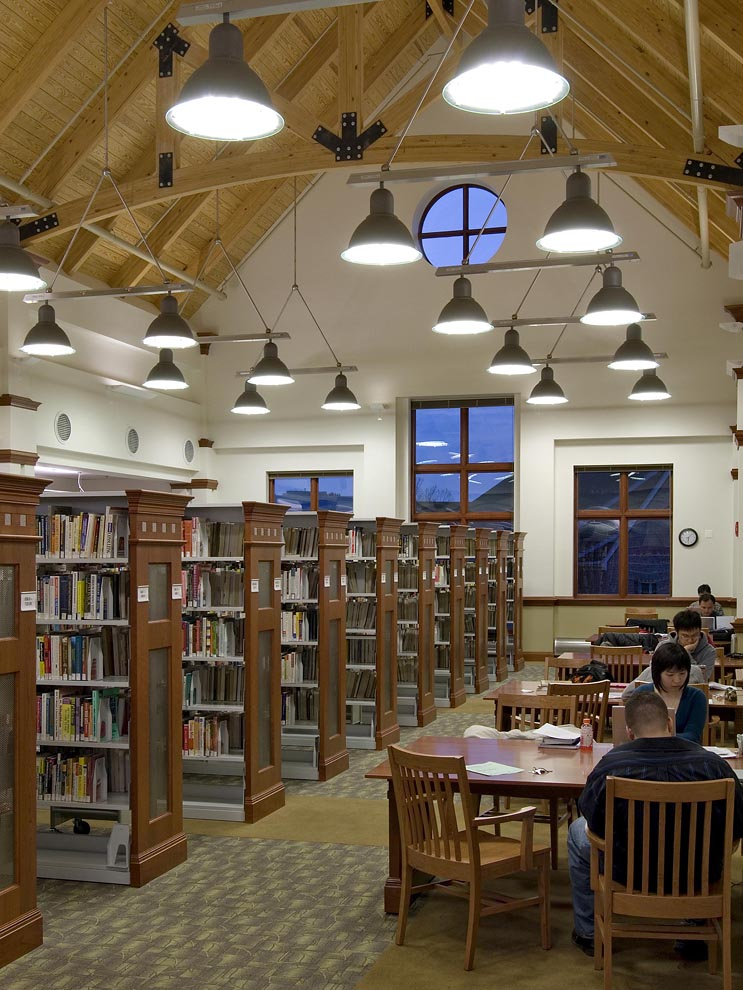 people studying at tables on right of book stacks