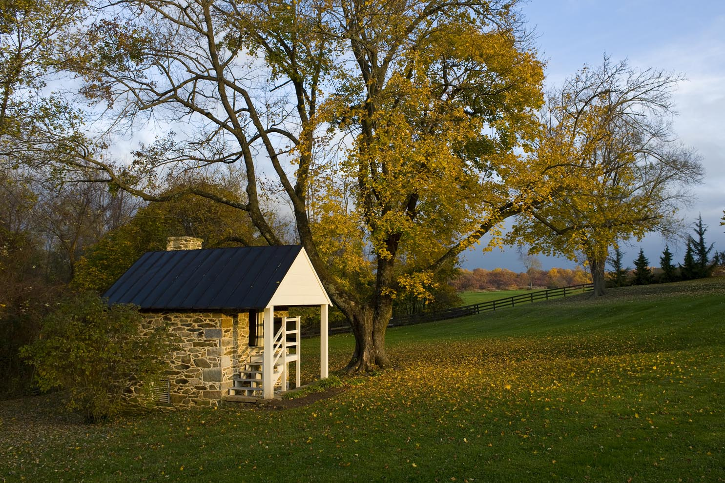 stone springhouse with fall foliage