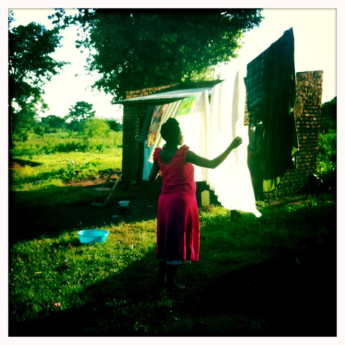 A woman hangs laundry in Takira, Uganda on May 29, 2012. Photo by Peter DiCampo.
