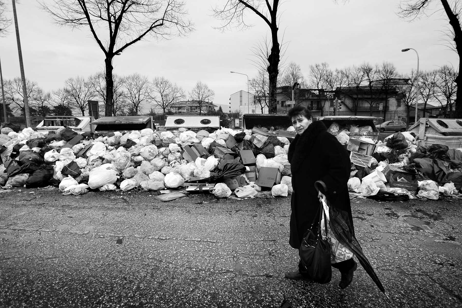A woman walks past a pile of garbage on a street in Caserta, Naples' neighbouring city, on February 21, 2008.