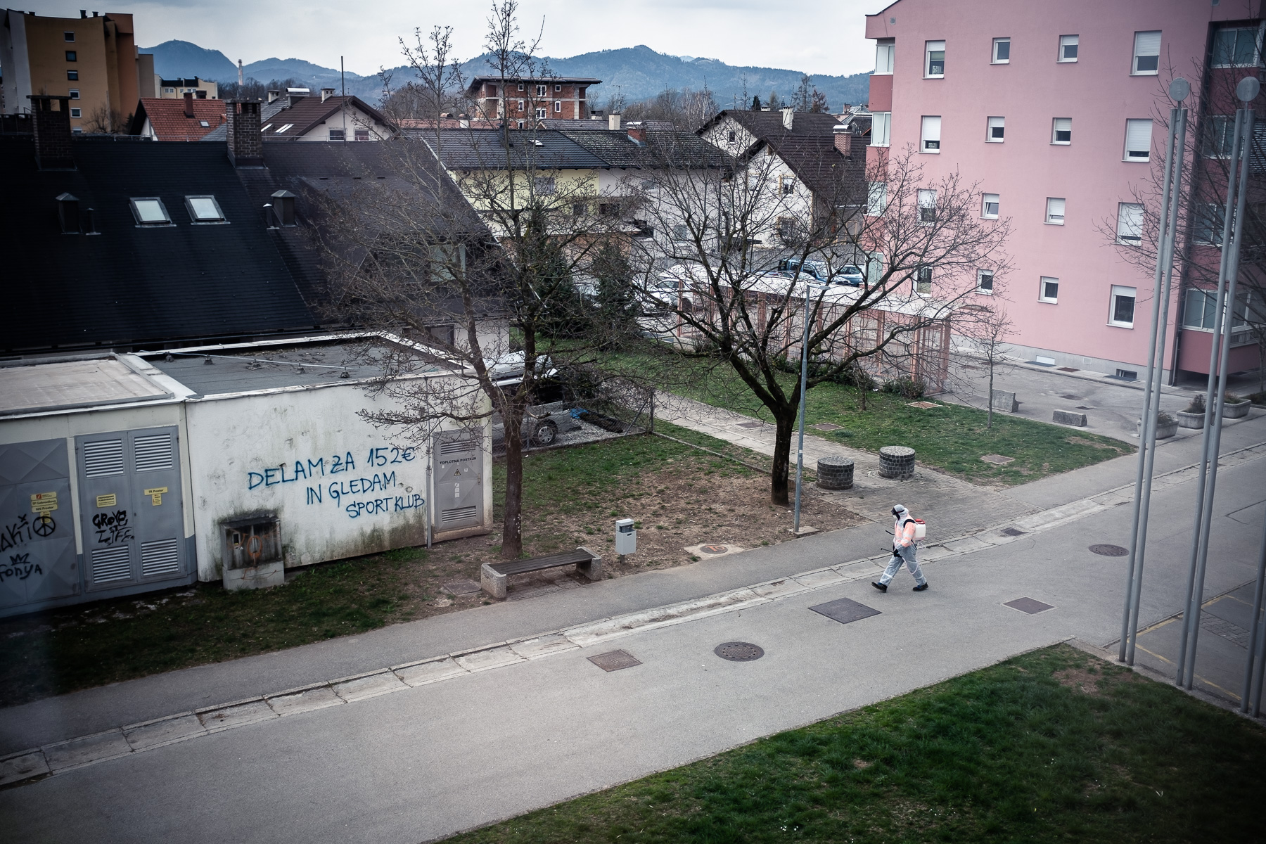 A man in full protective suit sprays disinfectant on public surfaces in Kranj, Slovenia, during a nationwide coronavirus lockdown, on March 24, 2020.