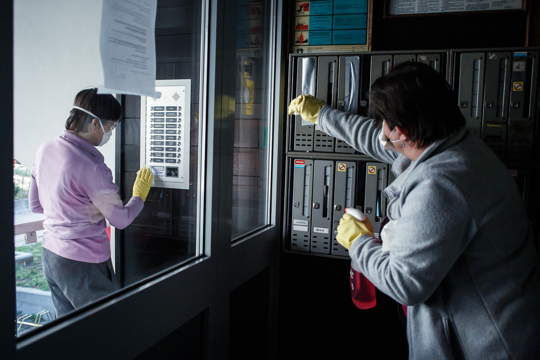 Residents of an apartment building in Kranj, Slovenia, disinfect the building during mandatory daily apartment building disinfection on April 3, 2020.
