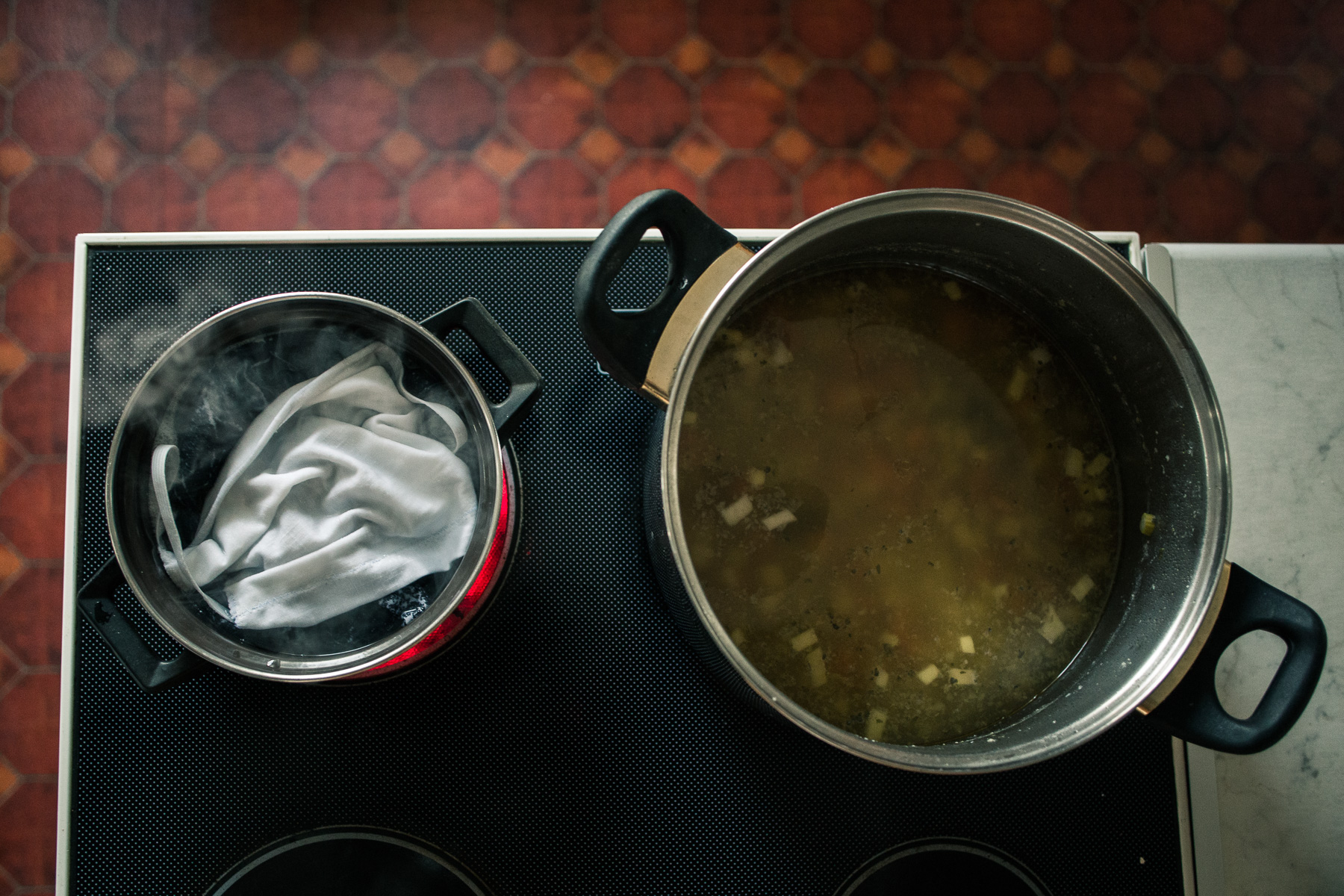 A homemade mask is washed and boiled after use next to a pot of vegetable soup on the stove.
