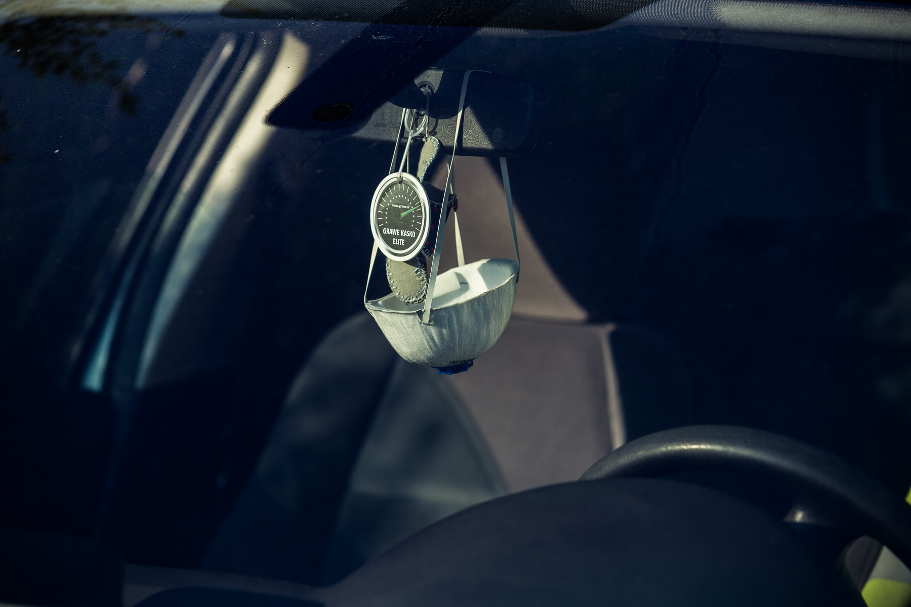 A protective mask hangs from a rear view mirror of a car in Kranj, Slovenia, on April 10, 2020.
