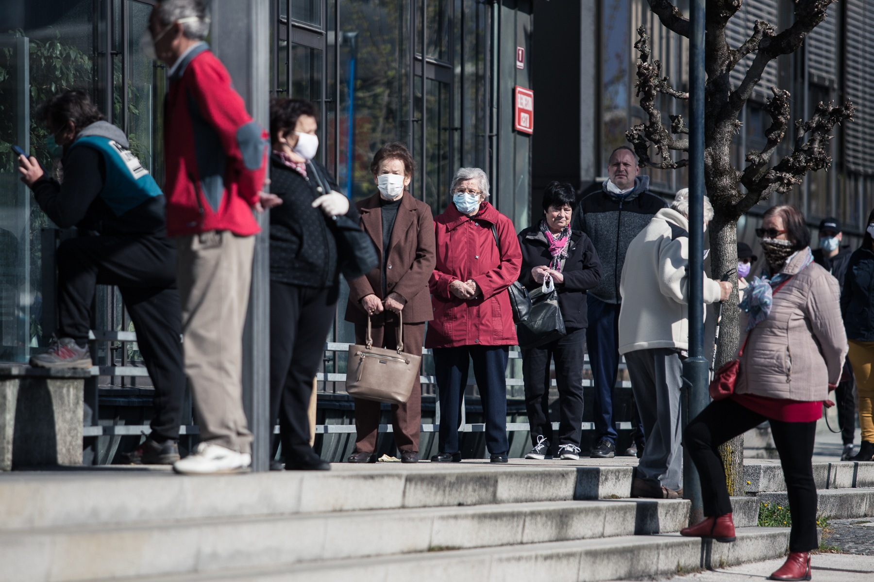 People wait in line to enter a bank in Kranj, Slovenia, due to limitations on how many people can be in the bank at the same time.