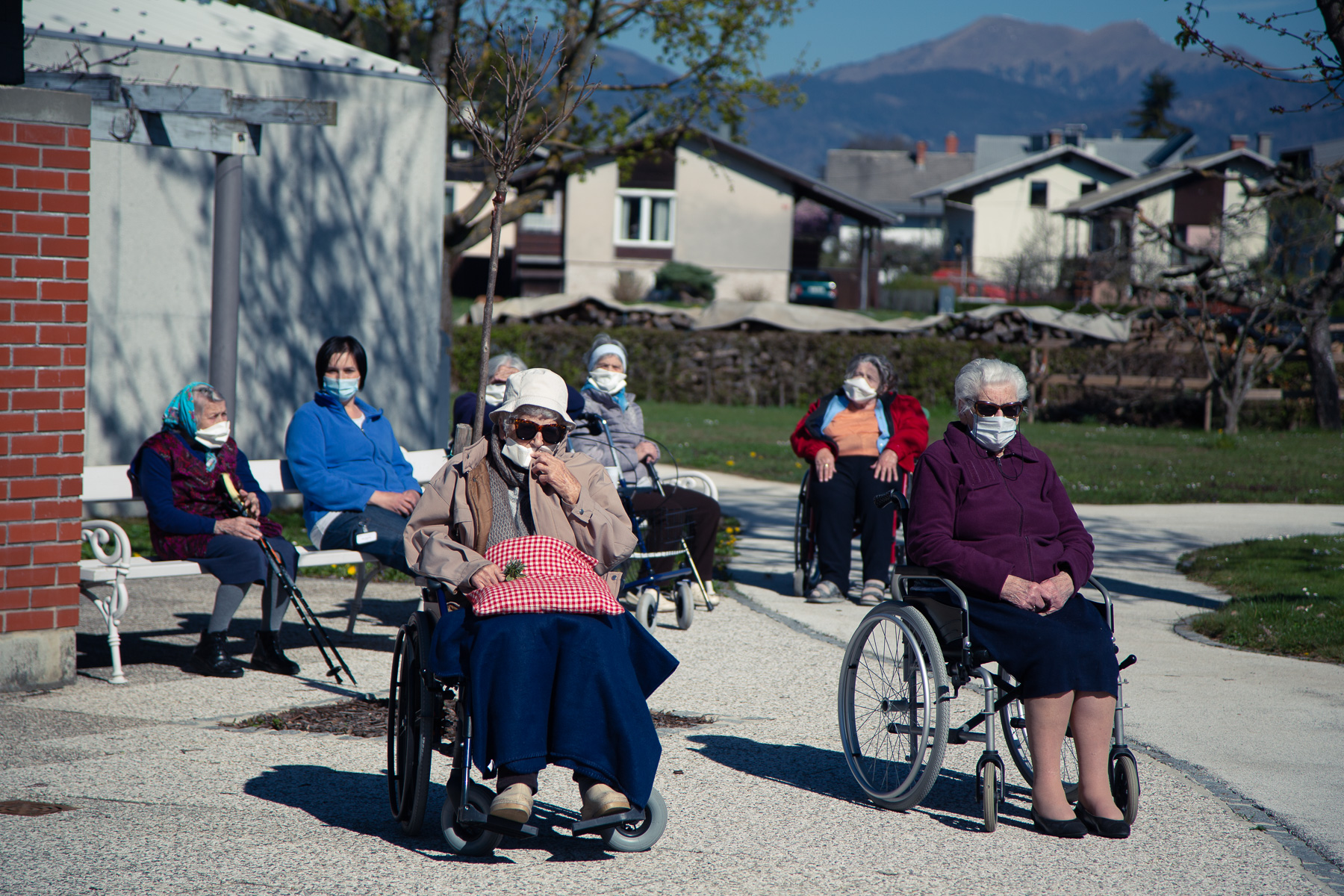 Seniors of dr. Janko Benedik nursing home in Radovljica, Slovenia, listen to a zitherist play outside the nursing home on April 16, 2020. Nursing homes face biggest difficulties in times of the coronavirus outbreak, because the elderly are at greatest risk of developing a life-threatening condition. Concerts like these brighten up their days in  quarantine.