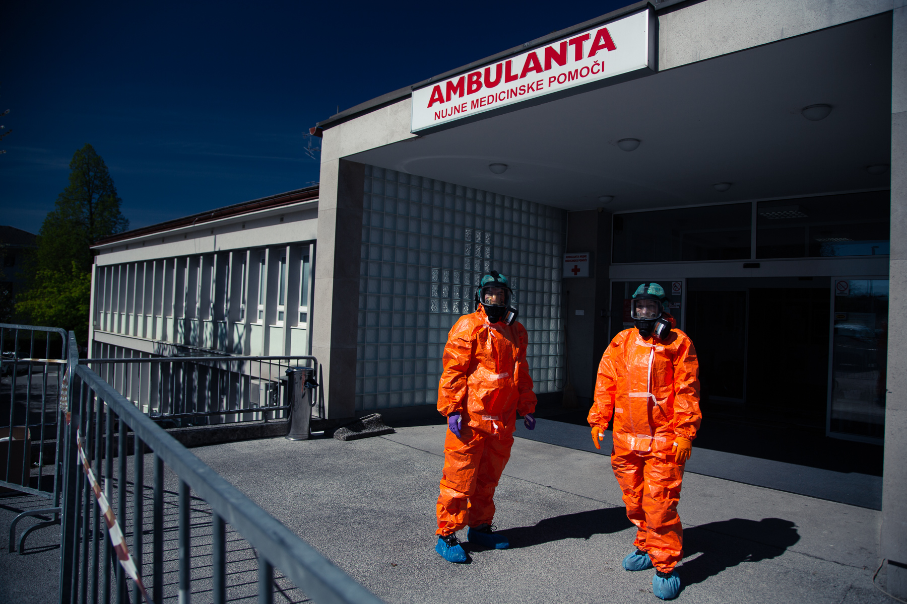 Medical personnel in hazmat suits wait at the COVID-19 testing site in Bled, Slovenia, for patients to arrive at a scheduled hour on April 16, 2020. Given the low frequency of tests in this small town, famous for its world famous tourist attraction Lake Bled, this system was put in place in order to save on protective equipment that needs to be discarded after each use.