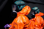 Medical personnel in hazmat suits wait to hand over a coronavirus swab sample at the COVID-19 testing site in Bled, Slovenia, on April 16, 2020.