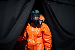 A medical worker in hazmat suit waits at the COVID-19 testing site in Bled, Slovenia, for patients to arrive at a scheduled hour on April 16, 2020. Given the low frequency of tests in this small town, famous for its world famous tourist attraction Lake Bled, this system was put in place in order to save on protective equipment that needs to be discarded after each use.