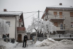 A man is trying to clean the ice in front of his house  in Postojna, Slovenia, February 5 2014.