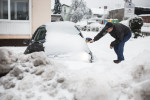 A man hammers his way through a thick layer of ice on his car in Postojna, Slovenia, February 5 2014.