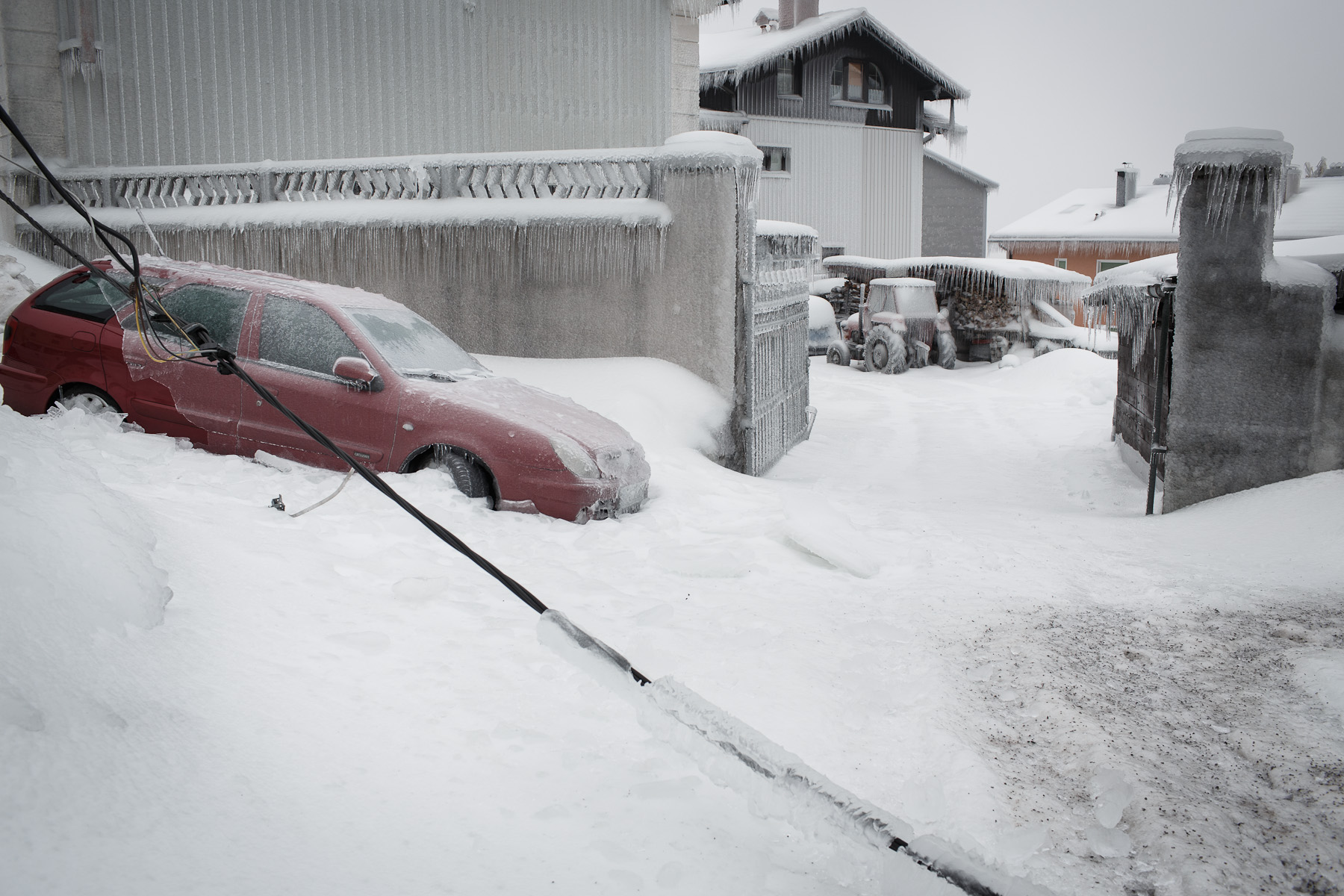 A broken power line cable and frozen vehicles are seen in Postojna, Slovenia, February 5 2014.