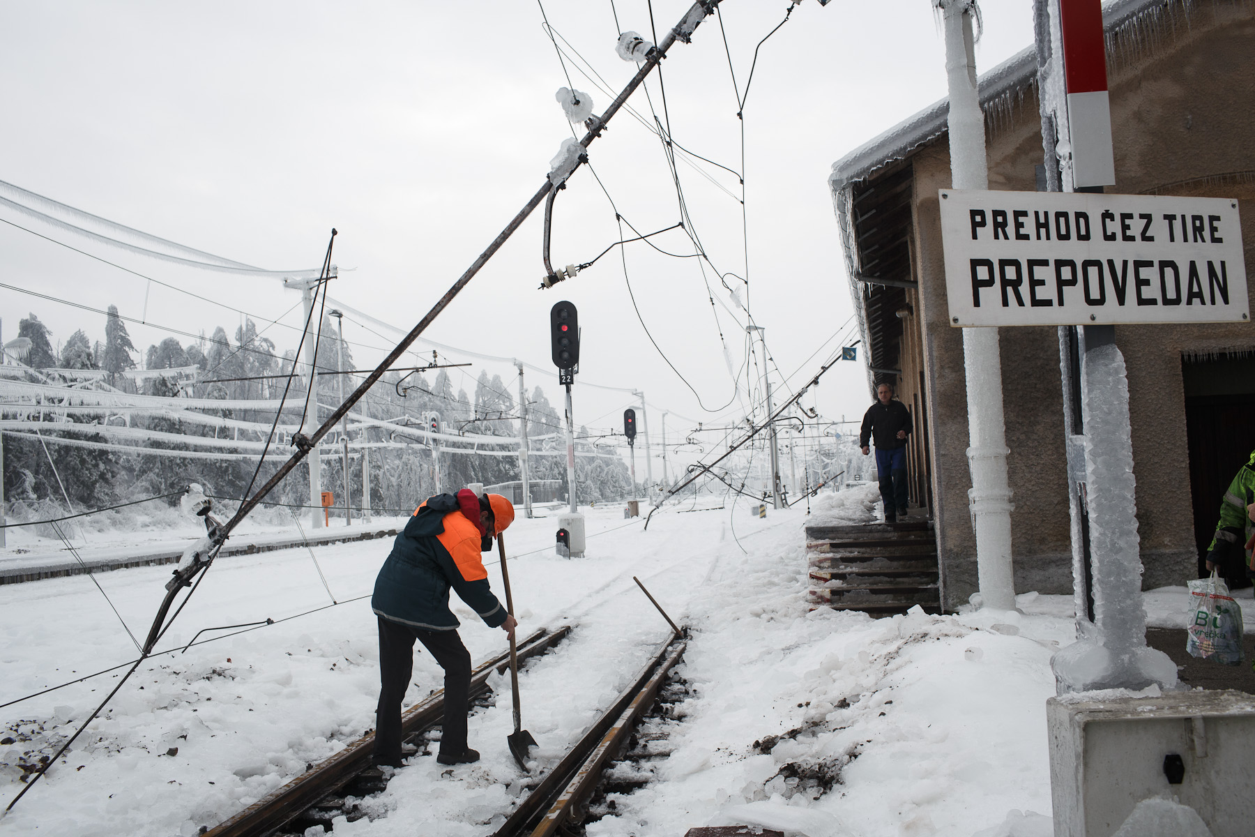 A worker clears ice from the railroad tracks on a heavy damaged train station in Postojna, Slovenia, February 5 2014.