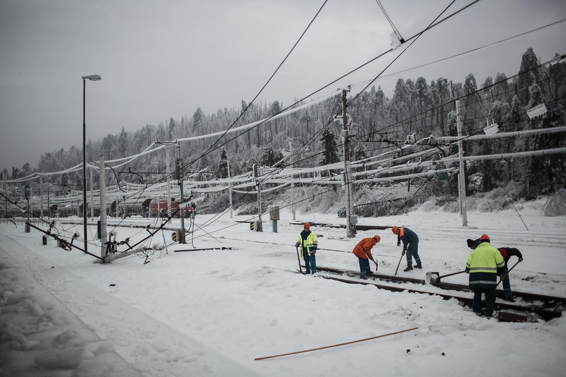 Workers clear ice from the rails on the heavy damaged train station in Postojna, Slovenia, February 5 2014.