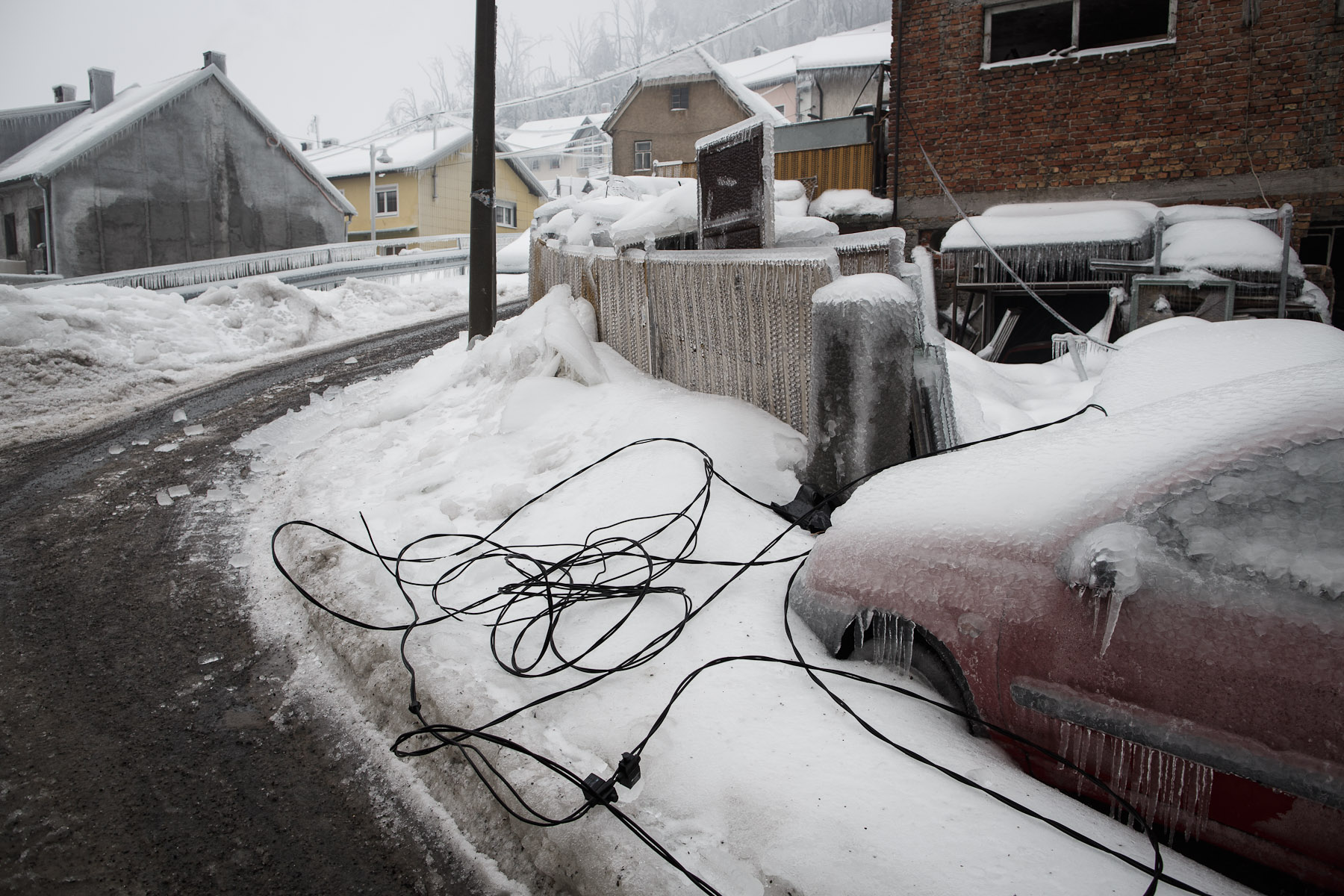 Torn-off power line cables lie around a frozen car in Postojna, Slovenia, February 5 2014.