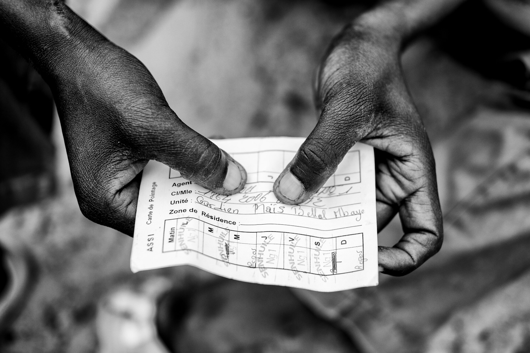 Employee in the Senhuile/Senethanol shows his presence checklist in one of the villages in the Ndiael region of Senegal, on January 8, 2014. The checklist serves as the basis on which the company pays him for his work. Out of 4500 jobs that were promised by the company, Senhuile/Senethanol is currently employing around 200 people, 20 of them are women. The man is employed as a guard, receiving payment of 3000 Senegalese francs /4,5 Eur/ for a  day and 4000 Francs /6 Eur/ for a night shift. He does not have an official employment contract with the company; the company also does not pay social security or insurance for him. The payment is not regular and is often lower than promised.