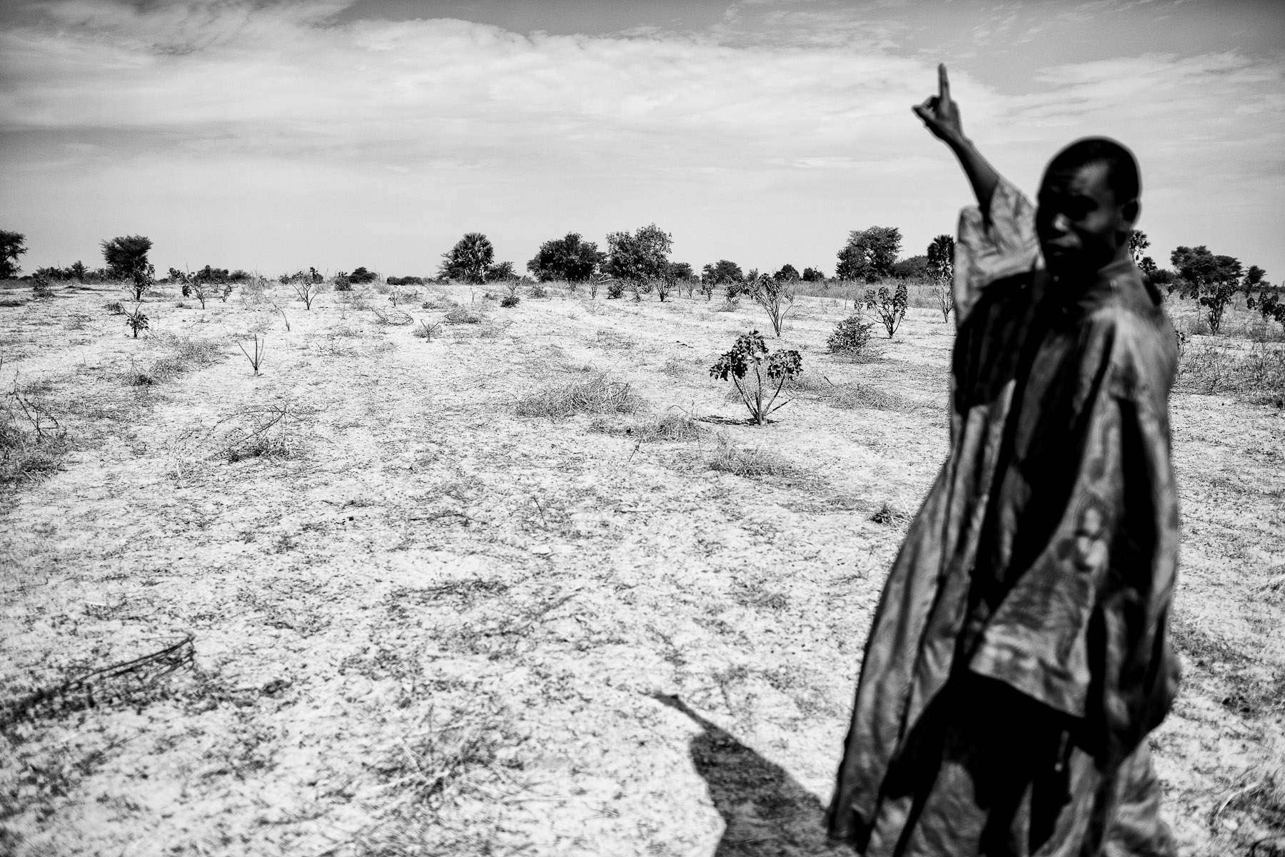 A villager shows the land near the village of Colobane, Senegal, that has been, presumed illegally, acquired by the Italian company African National Oil Corporation (ANOC) to grow Jatropha plants for biofuels, January 10, 2014. In Senegal, traditional land, including majority of the land in the region of Kaolac, is not owned by the individual or a family, but is a property of local community. Therefore, anybody who wants to legally sell or buy the land needs the approval of the local Council. At this moment, there is no evidence that ANOC gained approval from the Council for their land deals, which means that the legality of their ownership over the land is seriously questioned. Furthermore, the land deals have been done in a very non-transparent manner with villagers signing blank or uncompleted papers as their agreement for selling the land. None of the villagers received a copy of the document they signed.