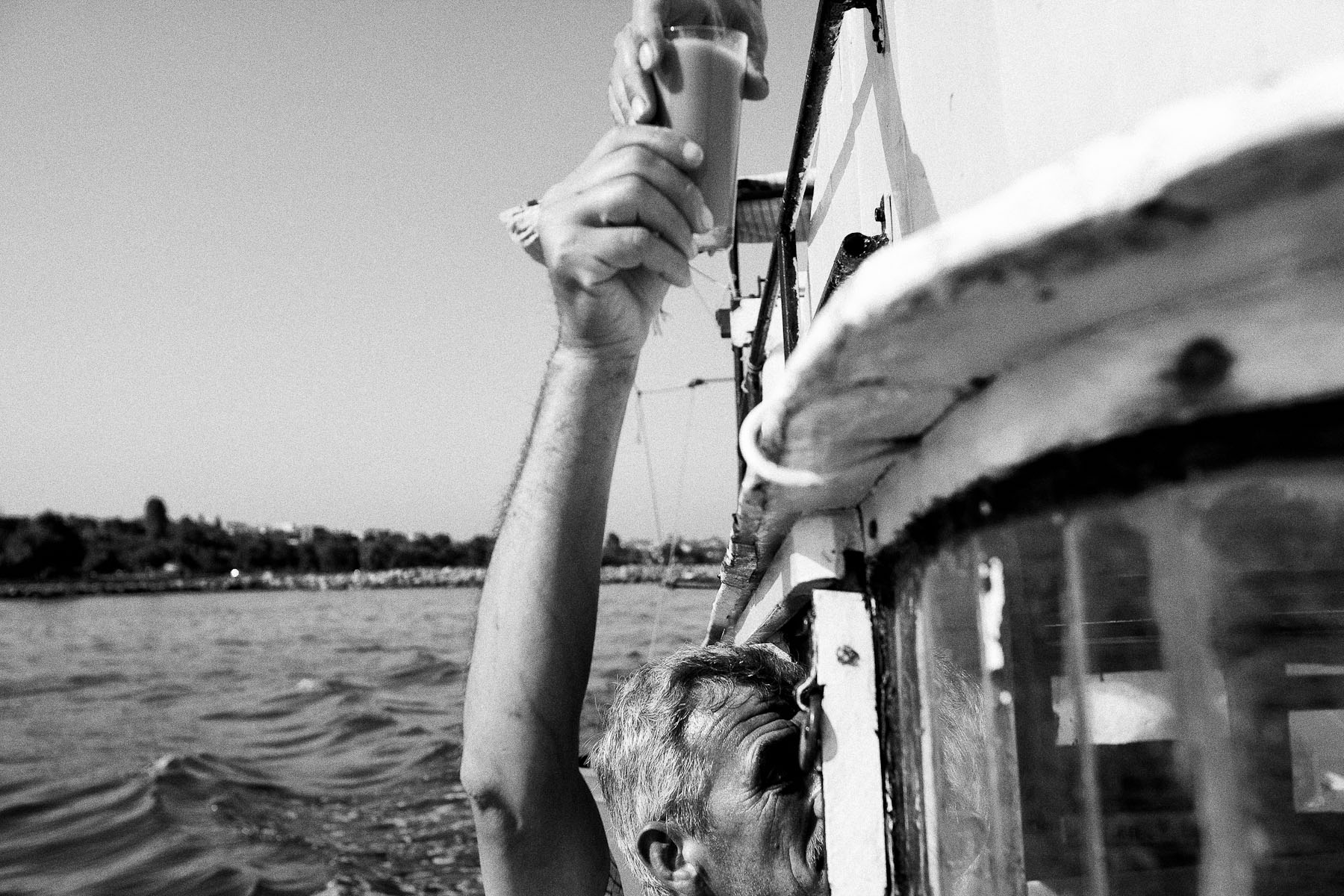 Cevat Sariaydin hands a cup of coffee to Adem Golak, who is steering the boat on the tiny rooftop cabin, as they head out to fish on the Marmara sea on 21st June 2010. Coffee is the basic tool for staying awake and alert all throughout the night, when they fish because it is cool enough for the fishermen and the fish.