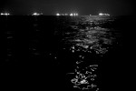 When the night falls, the small boat is a tiny light on a moonlit sea scattered with bright lights of tens of cargo ships.