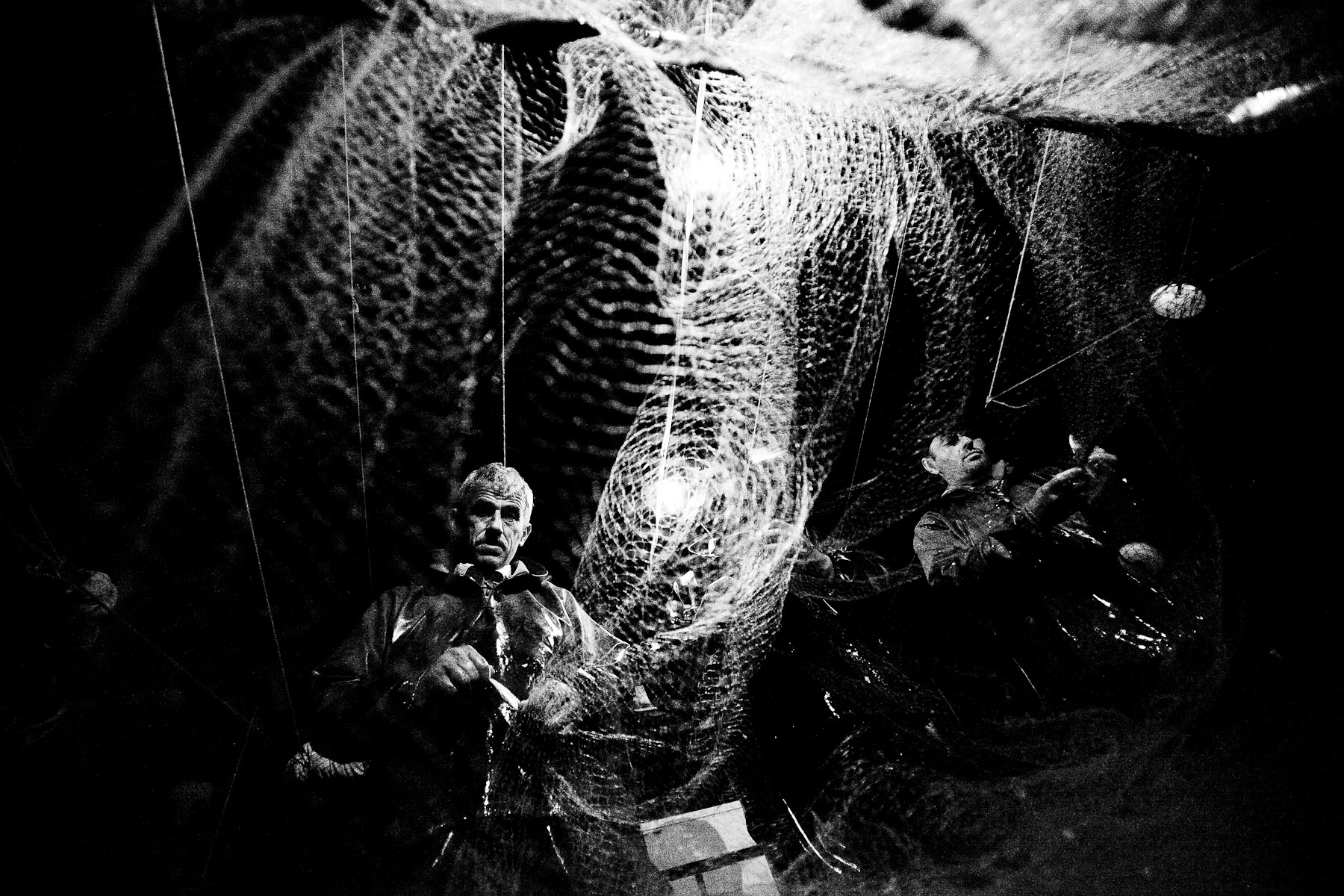 Adem, Cevat and Cinar pull the net from the Marmara sea off the coast of Istanbul on 22nd June 2010. They fish all throughout the night, because the air and sea are cooler and the fish are more likely to be in low depths.