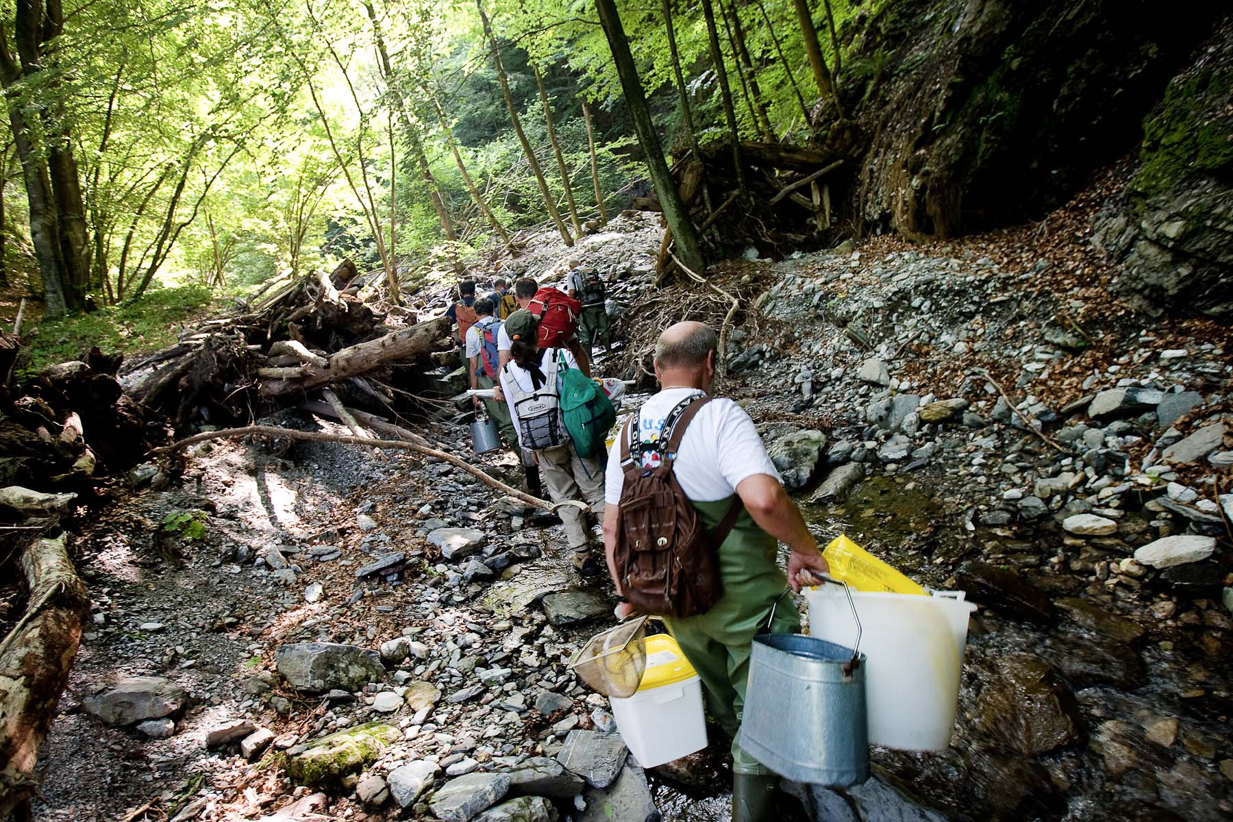 A team of fishkeepers, scientists and fishermen walks up a riverbed through a gorge littered by debree from a devastating flood months before. Monitoring of these streams runs twice a year for two weeks in at least seven difficult gorges.