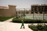 A worker passes a tennis court in a hotel complex in Hurgada, Egypt, on April 27, 2008. Hotel resorts in Hurghada, where tourism is the primary economy, are very green. Bushes, grass ... All of it needs extensive irrigation, because of heavy evaporation.