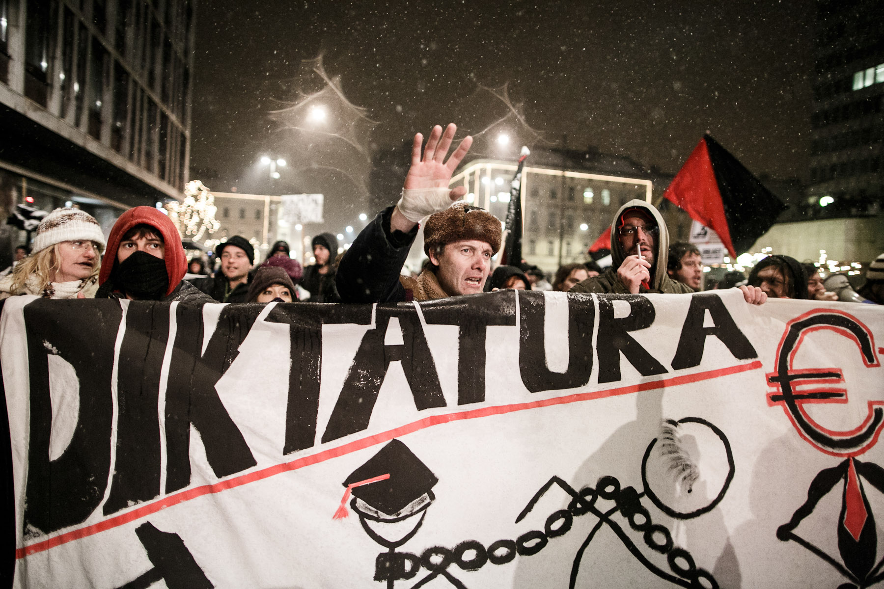 Protesters carry a large sign denouncing dictatorship of capitalism during anti-government protests on December 7 in Ljubljana, Slovenia.