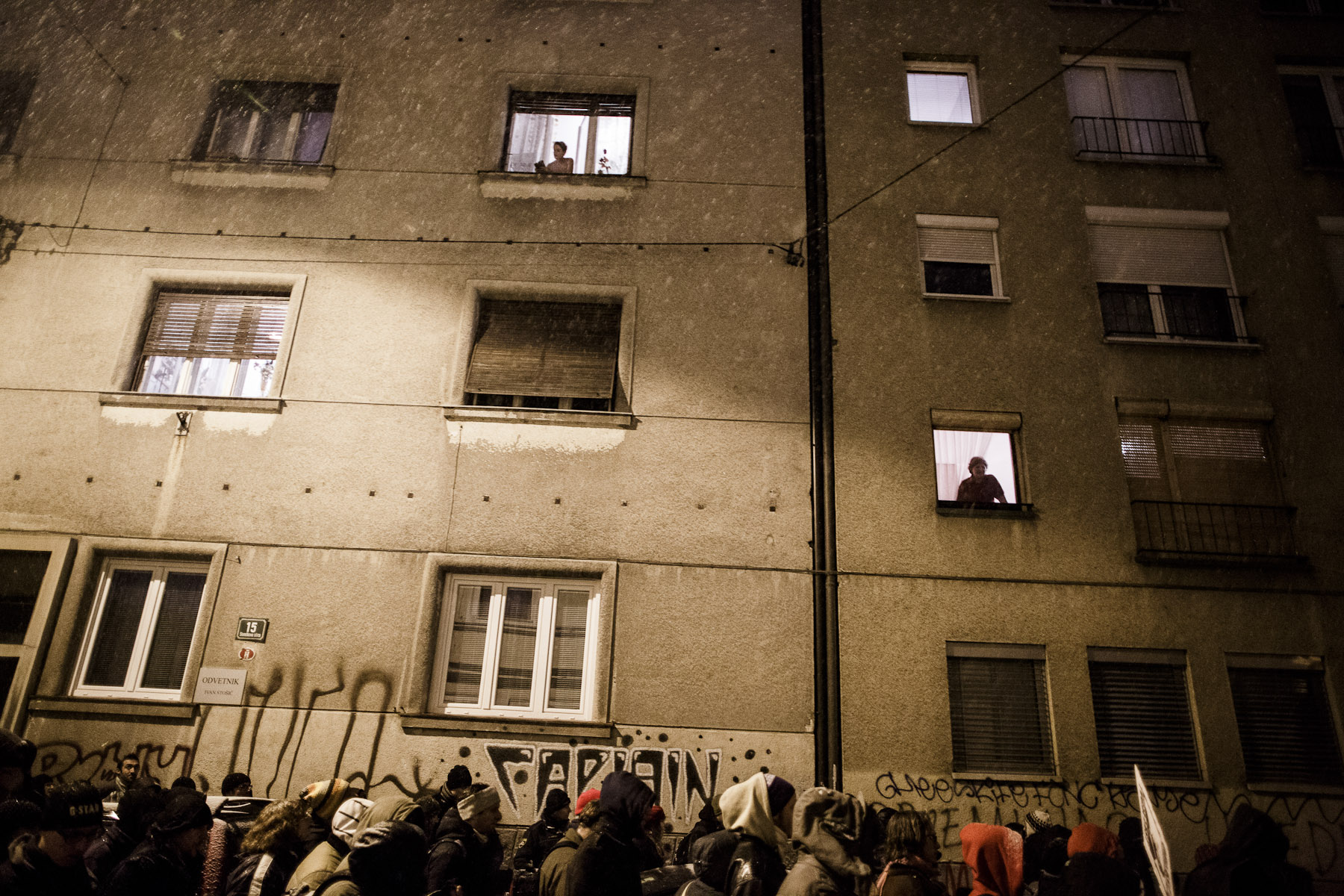 Protesters march through the streets as people watch from their windows during anti-government protests in Ljubljana, Slovenia, on December 7, 2012.
