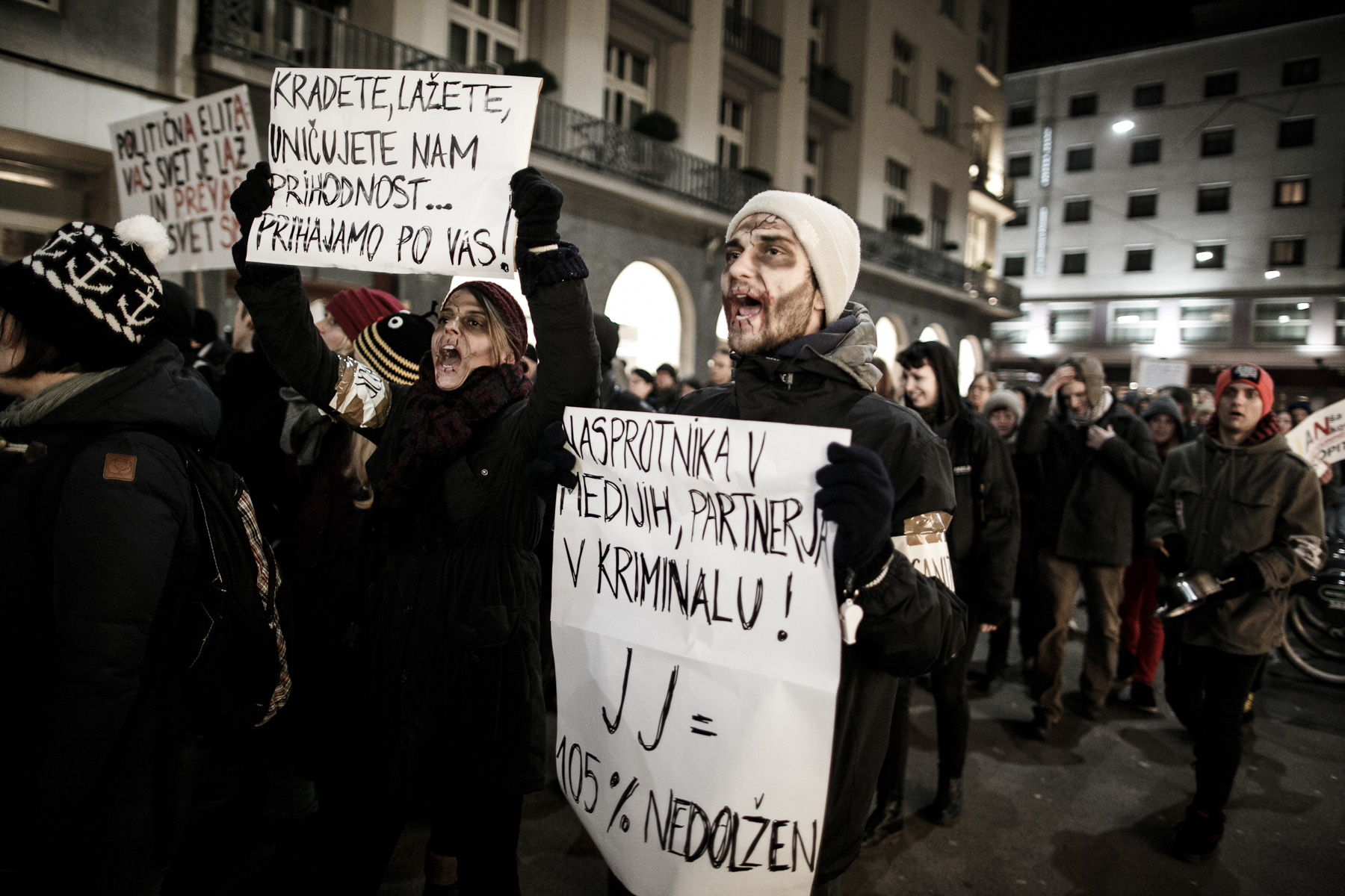 Protesters wearing zombie makeup march through the streets carrying signs that read {quote}You're stealing, you're lying, you're destroying pour future… We're coming for you!{quote} during a countrywide uprising in Ljubljana, Slovenia, on January 11, 2013.