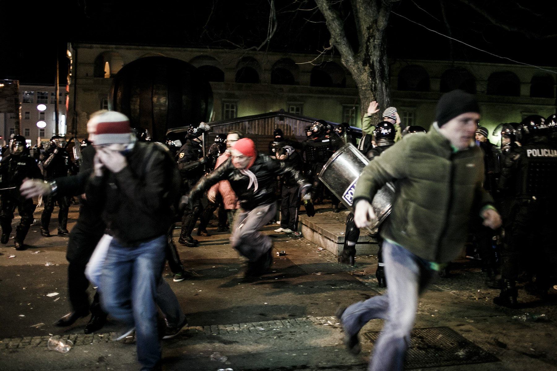 Protesters run as cobblestones and pyrotechnics start flying during protests against the mayor of Maribor Franc Kangler in Maribor, Slovenia, on December 3, 2012.