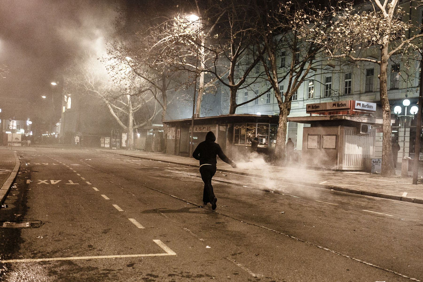 A protester carries a smoke bomb to throw to the police during protests against the mayor of Maribor Franc Kangler in Maribor, Slovenia, on December 3, 2012.
