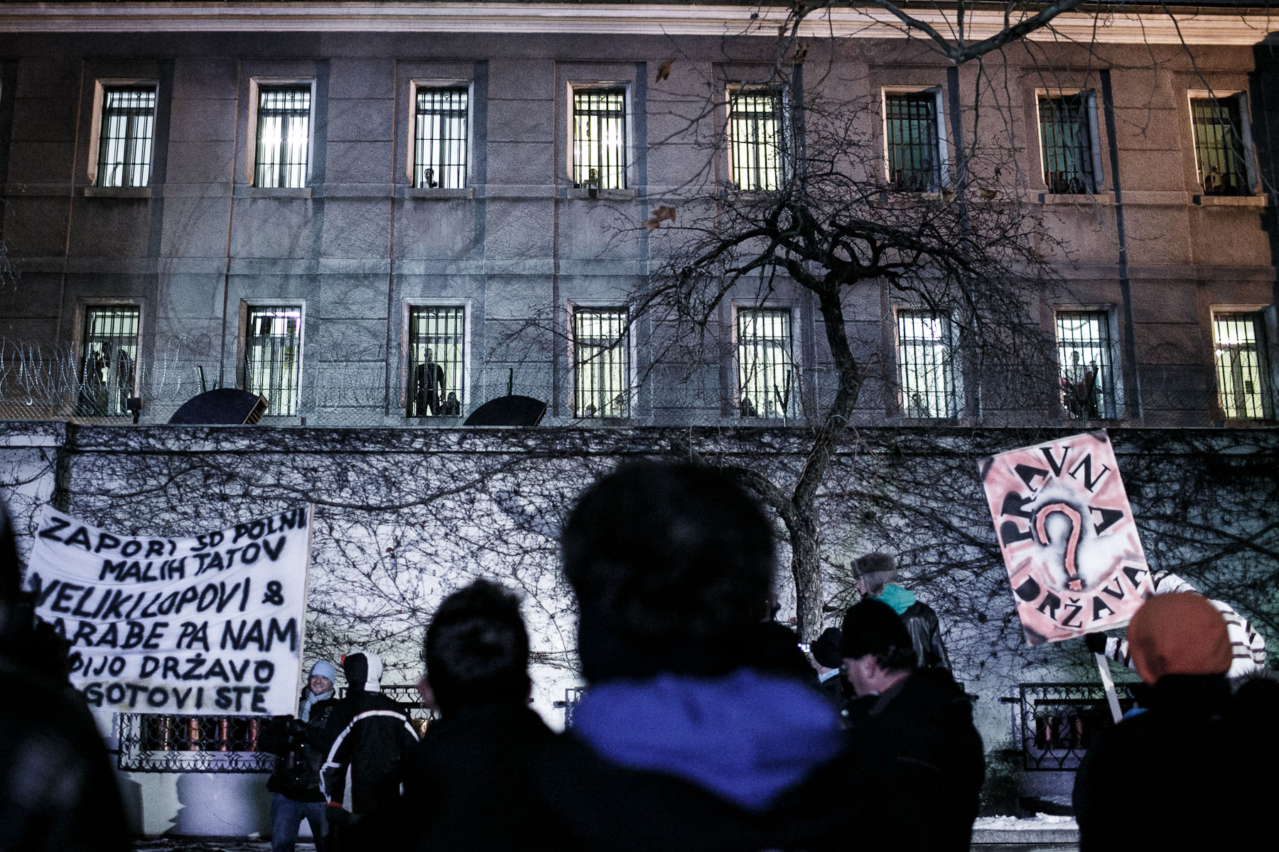 People protest outside the Maribor prisons demanding the release of protesters watching from the windows during a protest march against the mayor and the local government in Maribor, Slovenia, on December 14, 2012.