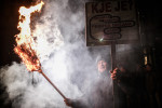A protesters carries a sign and a burning broom in front of a municipality building during a protest against the local government and the city council in Maribor, Slovenia, on January 7, 2013.