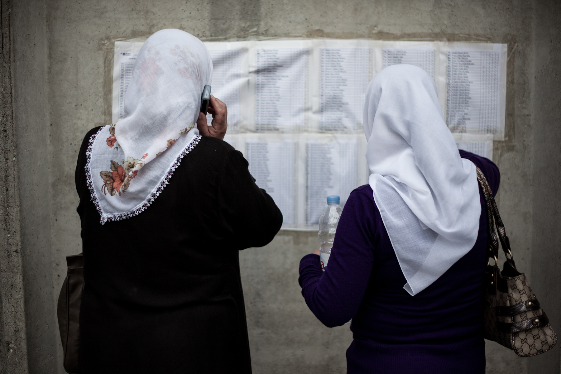 Bosnian women check the list of names of identified bodies in front of the Potocari memorial center, Srebrenica, July 10, 2010.