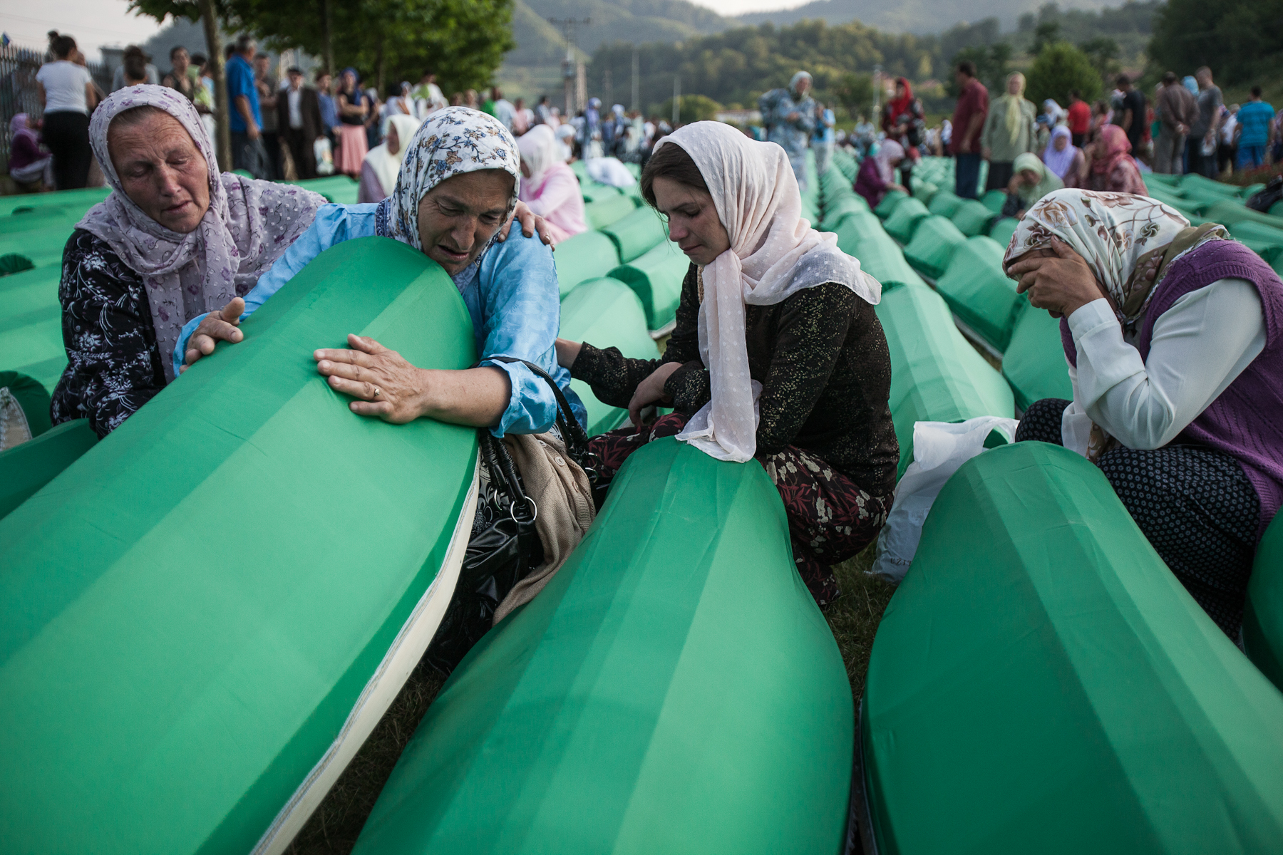 Women mourn among the lines of coffins at the Potocari cemetery in Srebrenica the day before the mass burial of 775 newly identified victims of the 1995 Srebrenica massacre.